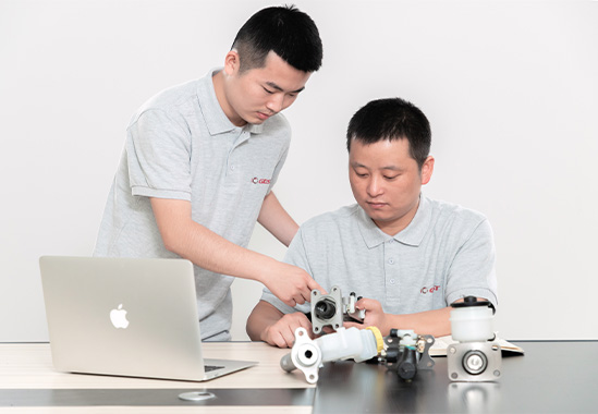 two engineers studying and comparing brake parts for customization