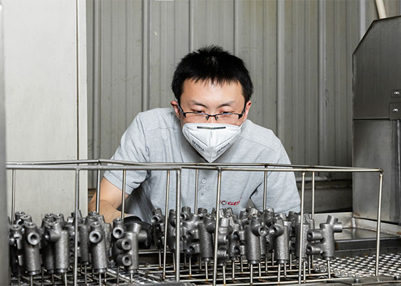focused worker looking at brake parts for strict production