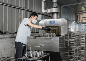 a worker proceeding ultrasonic cleaning of brake parts